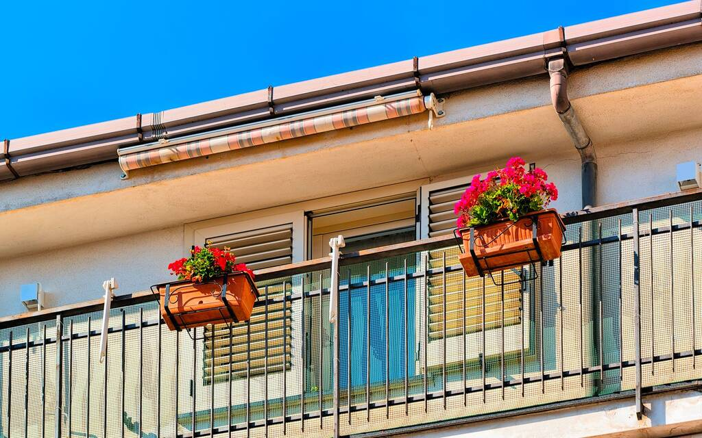 Italian vintage balcony for decoration design. House and home residential architecture details with plants and flower pots on Amalfi coast in Italy. Urban apartment flat building facade exterior.
