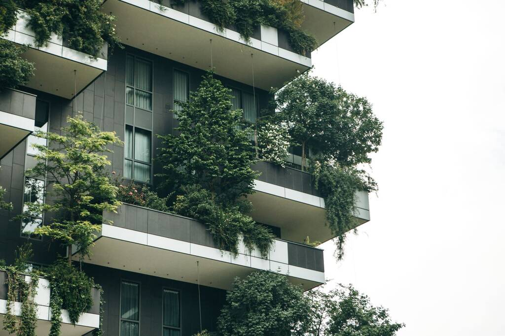 Italy, Milan, May 29, 2019: Trees grow on the balconies of a residential building. The environment and everyday life.