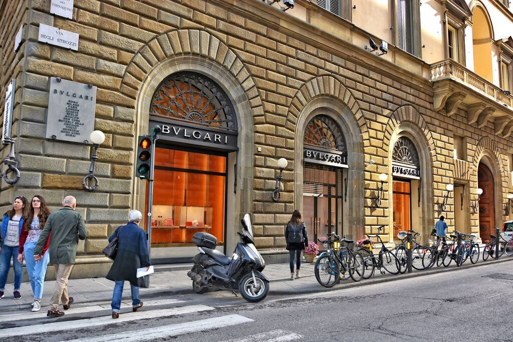 Shopping in Florence. Exterior of BULGARI store. Fine Italian jewelry, watches and luxury goods. People walk along a street. Parking lot with bicycles. Urban landscape. Italy, Florence – April 17,2018